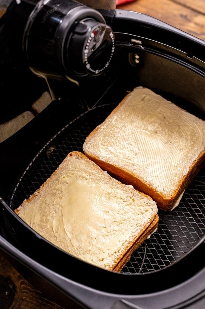 Two grilled cheese sandwiches in air fryer before cooking.