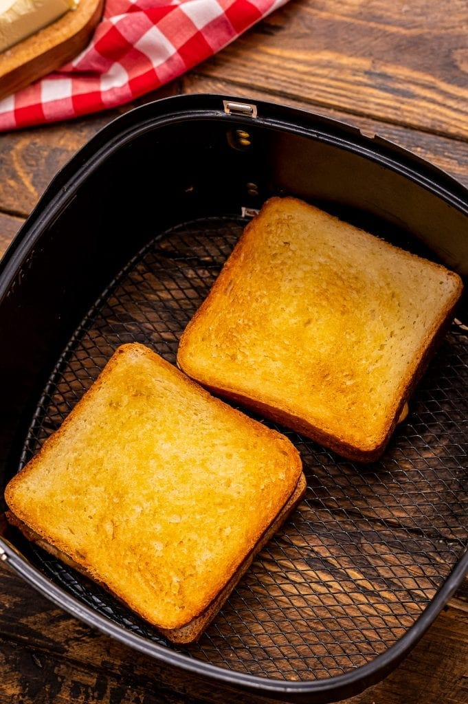 Two grilled cheese sandwiches in air fryer after cooking.