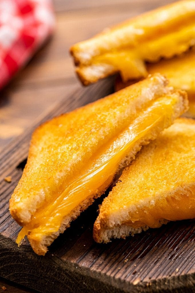 Diagonally cut slices of grilled cheese with one stacked slightly on top of the other.