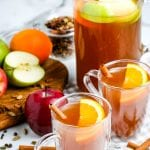 Apple Cider in glass mugs garnished with orange slices and cinnamon sticks. Pitcher in background that's full.