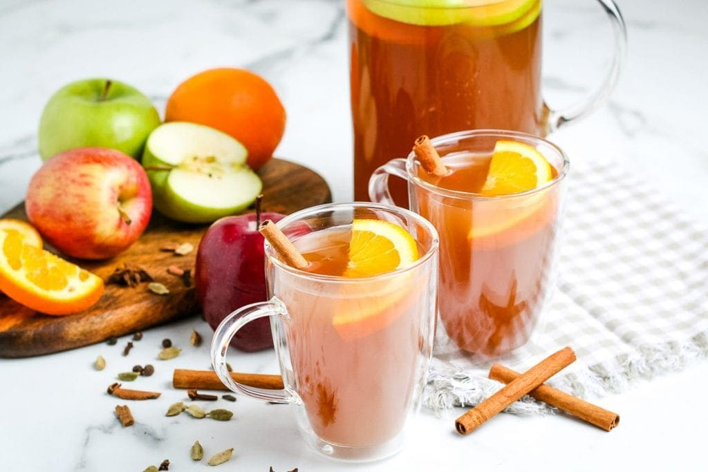Two glass mugs with apple cider. Garnished with cinnamon sticks and oranges. Pitcher and sliced apples and oranges in background.