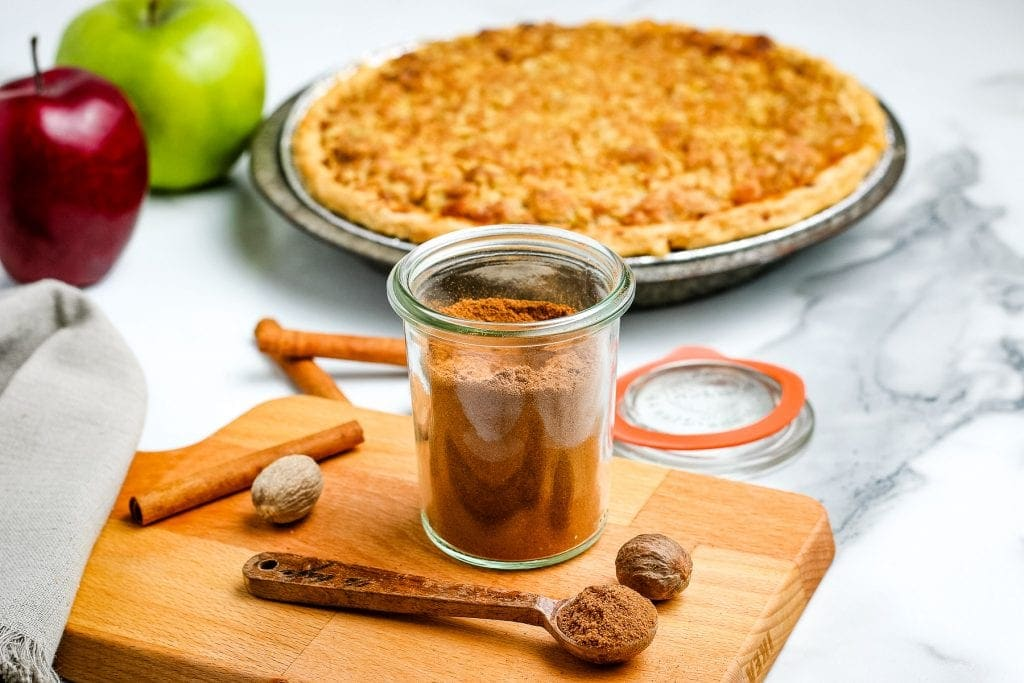 Homemade Apple Pie Spice in a glass container sitting on wooden cutting board and apple pie in background.