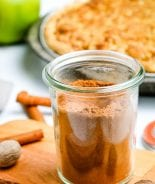Glass jar on light wooden board with apple pie spice in it and pie in background.