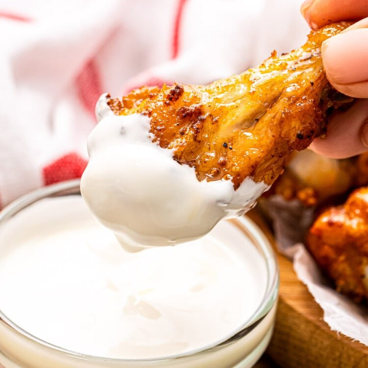 Hand holding chicken wing that is dipped in ranch
