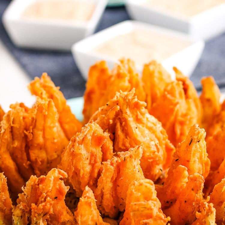 Close up photo of a blooming onion with small square dishes of dipping sauce in background