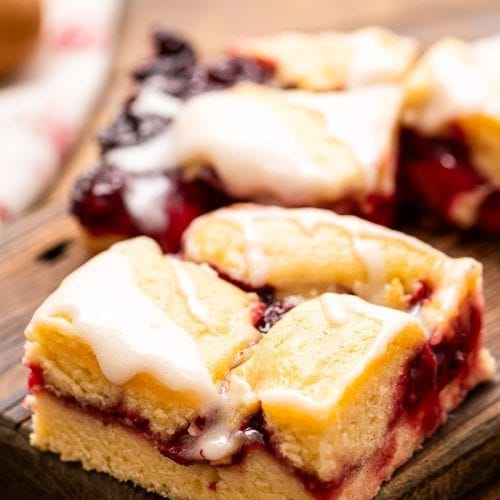 A sliced piece of Cherry Pie Bars on a wooden cutting board with another behind it.