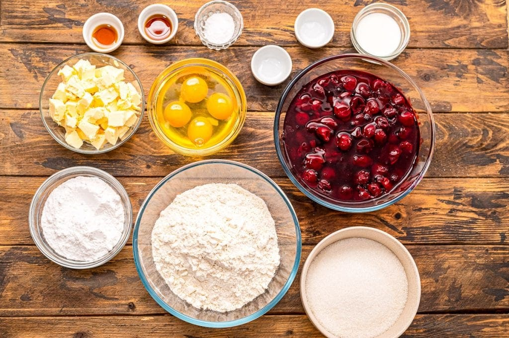 Overhead image of ingredients for Cherry Pie Bars in glass baking dishes