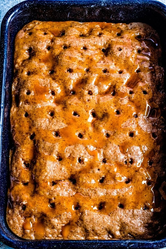 Dulce de Leche Apple Poke Cake with holes poked in it and dulce de leche drizzled over it.
