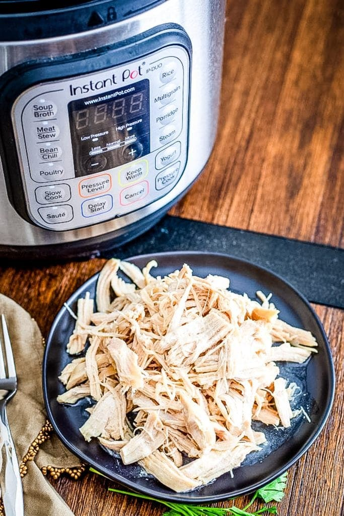 Shredded chicken on dark plate with an Instant Pot in background