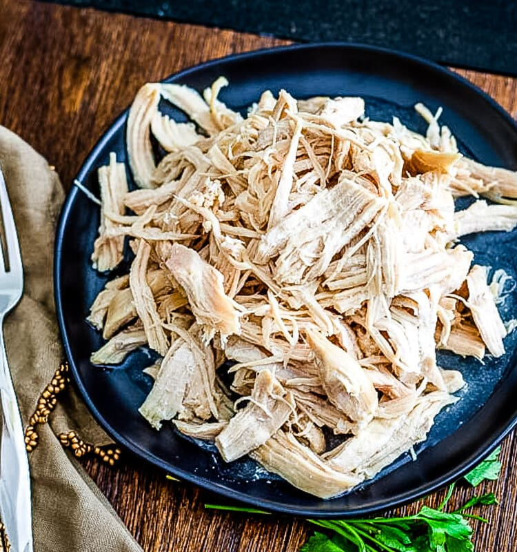 Overhead view of a plat of shredded chicken with a tan napkin with fork on top of it next to it.