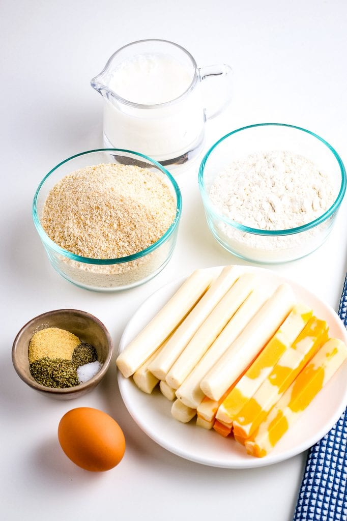 Ingredients for Mozzarella sticks including an egg, seasonings, plate of cheese sticks, bowls of bread crumbs and flour along with a jar of milk.
