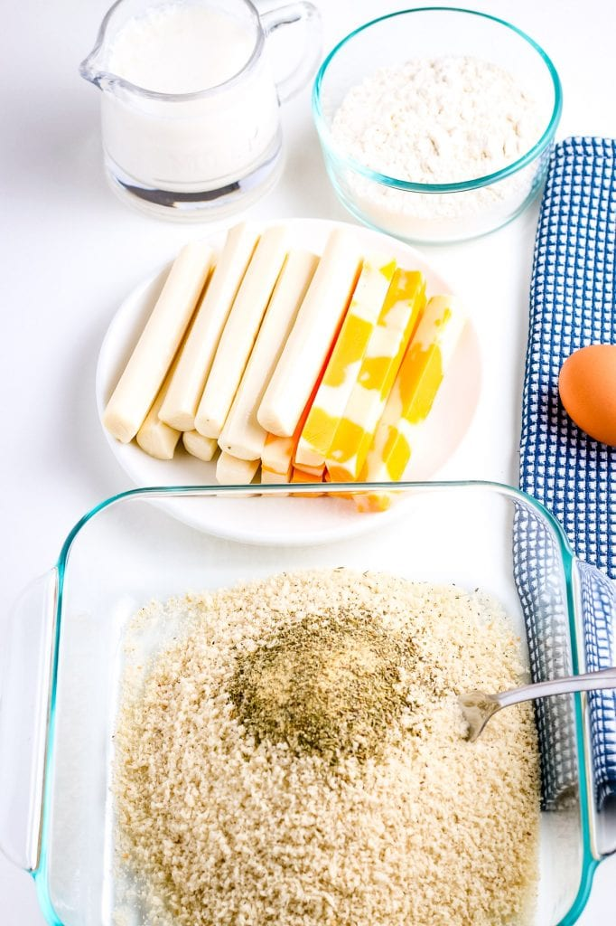 Bread crumbs with seasonings and a spoon in glass baking dish. In background a plate of cheese sticks, dish of flour and glass jar of milk.