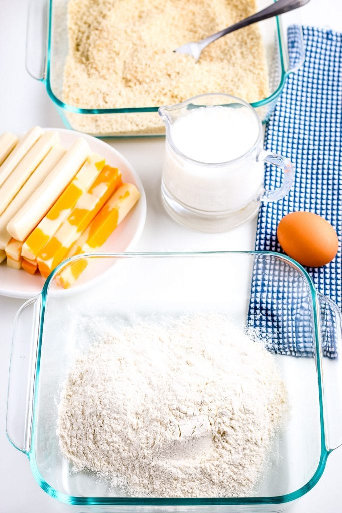 Glass baking dish with flour. In the background a plate of cheese sticks, jar of milk, egg on blue napkin and a glass dish of bread crumbs.