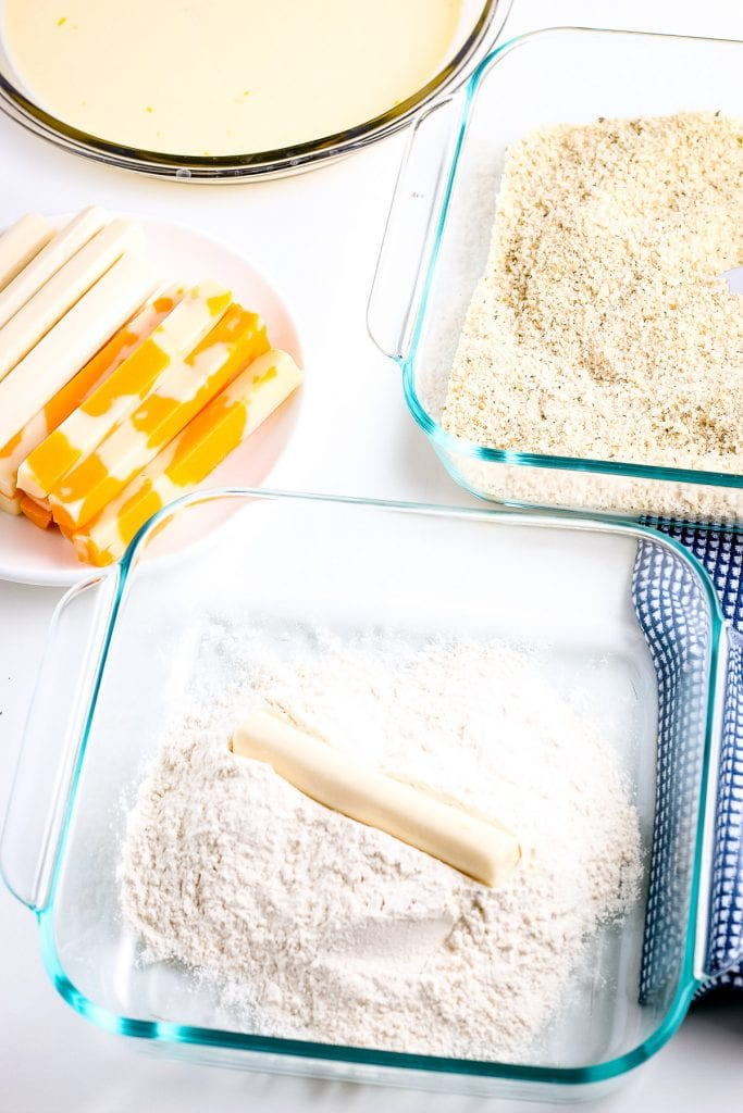 Cheese stick being rolled in flour mixture with cheese sticks, bread crumbs in glass dish and a bowl of mixed eggs in background.