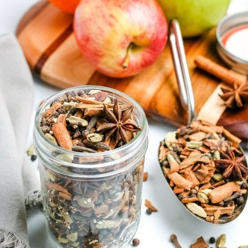 Mulling Spices in glass jar with apples behind it.