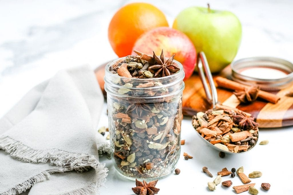 Mulling Spices in glass jar with apples, spices, and napkin background.