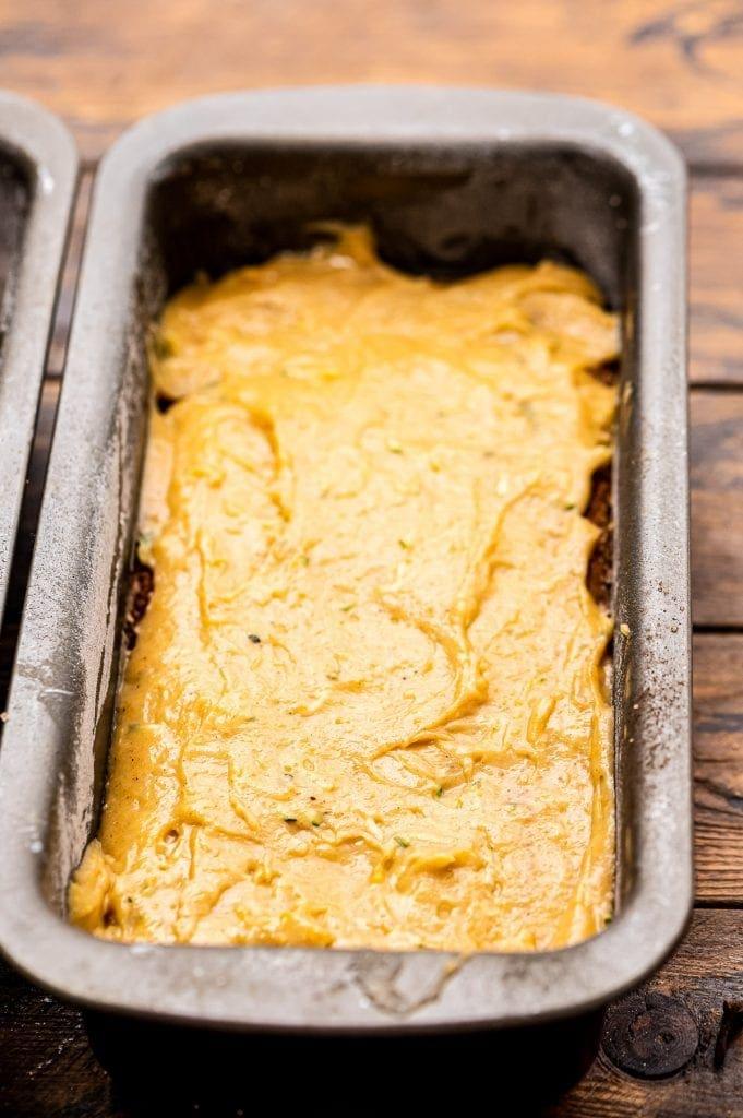 Metal loaf pan with pumpkin zucchini bread in it.