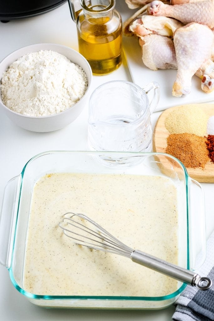 Buttermilk batter whisked together in square clear dish with whisk in dish.