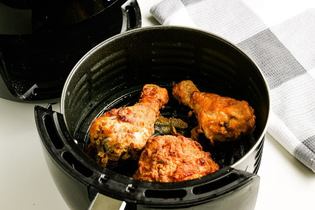 Fried Chicken that is cooked in black round air fryer basket.