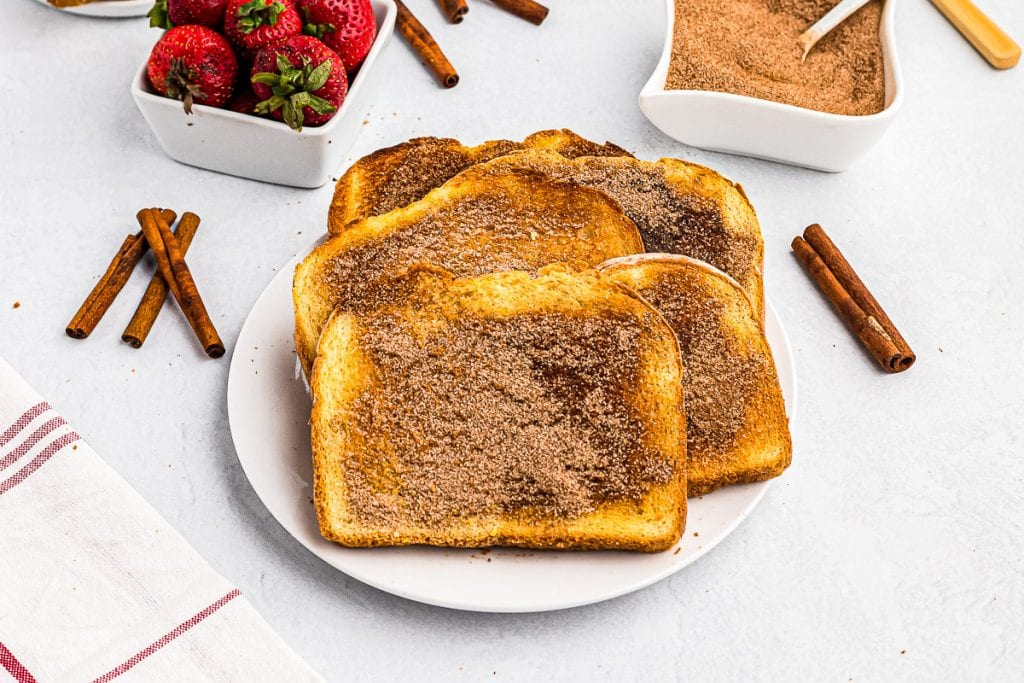 Buttered toast with cinnamon sugar on it stacked on plate.
