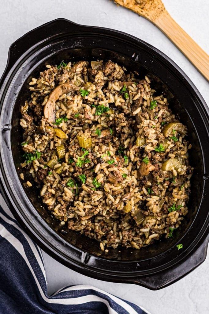 Black Crock Pot with Crock Pot Hamburger Wild Rice Casserole in it.