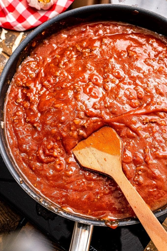 Meat sauce in black skillet with wooden spoon