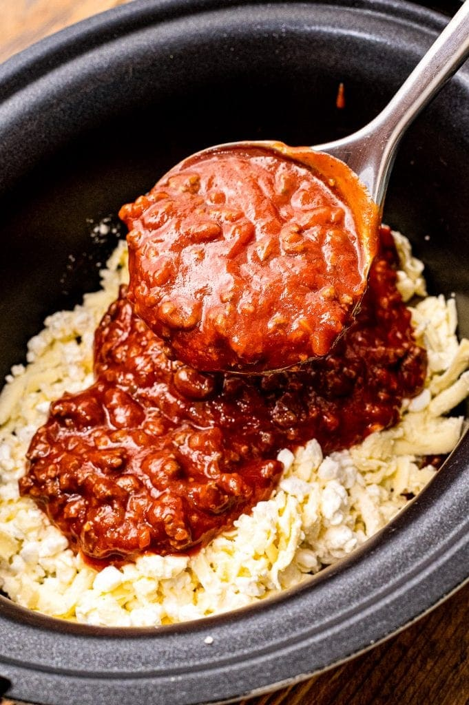Spoon ladling meat sauce on top of cheese in crock pot
