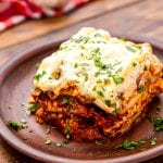 Small wooden plate with a piece of lasagna on it garnished with parsley on wooden background.