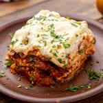 Piece of prepared lasagna on wooden plate