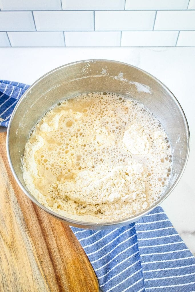 Metal bowl with yeast mixture added to flour mixture.
