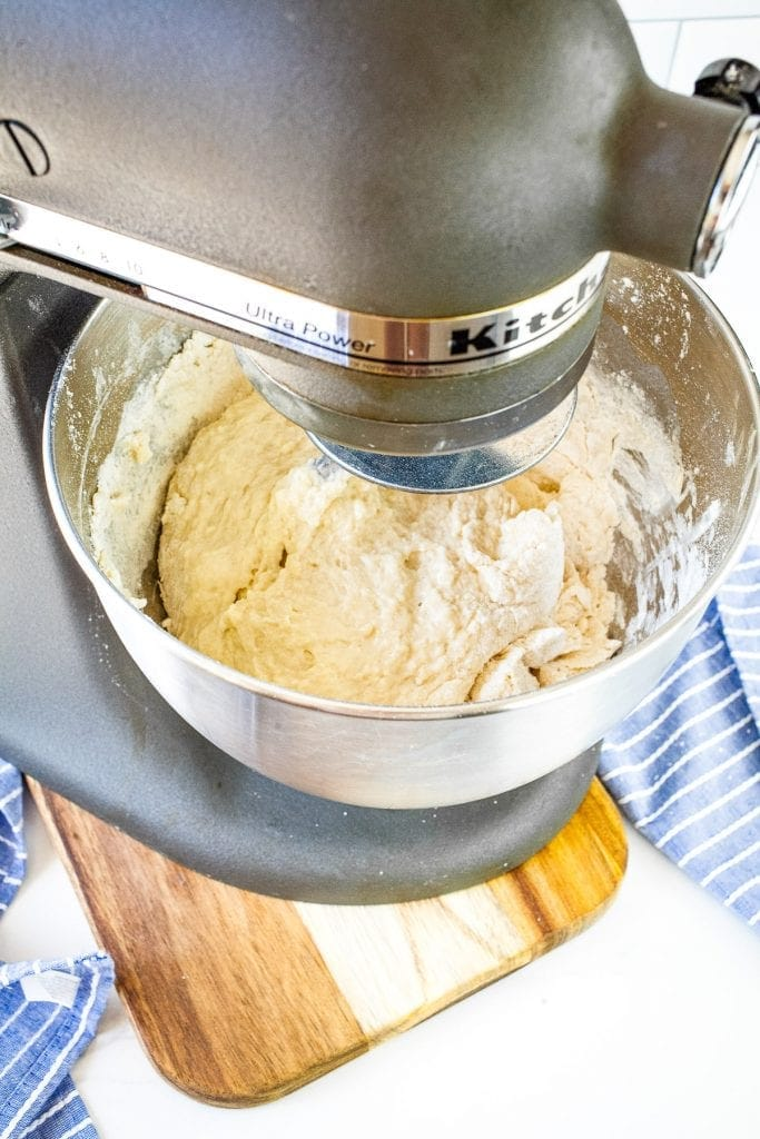 Whisk of stand mixer mixing dough ingredients together