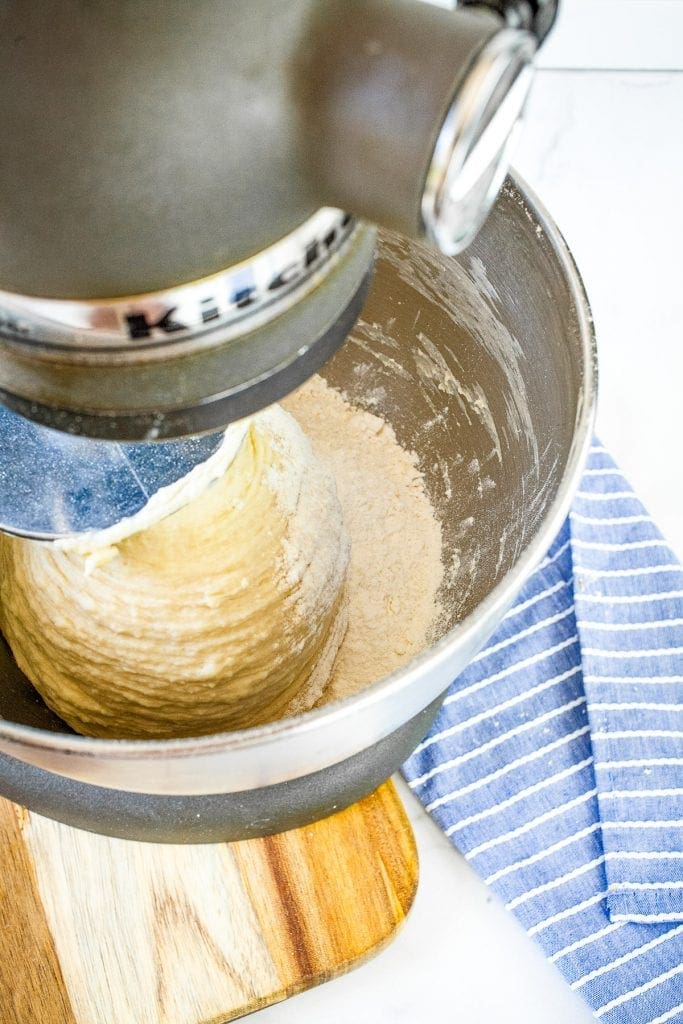 Stand mixer mixing together dough in metal mixing bowl
