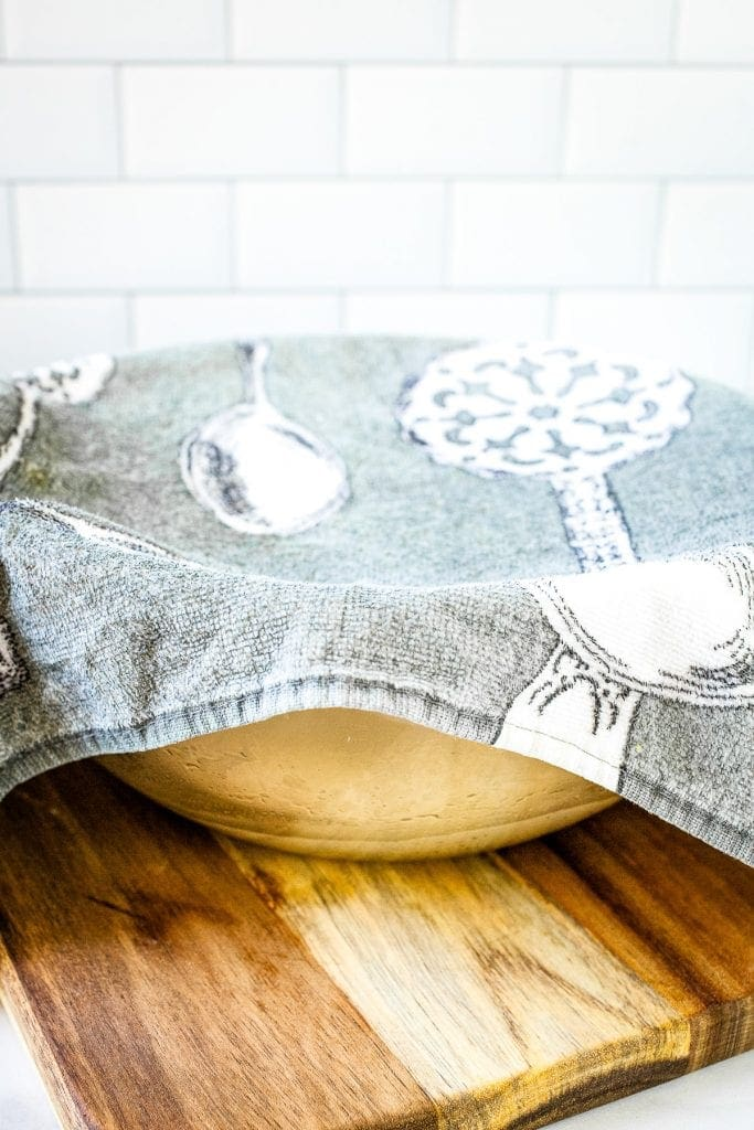 A glass bowl with dough in it covered by a kitchen towel