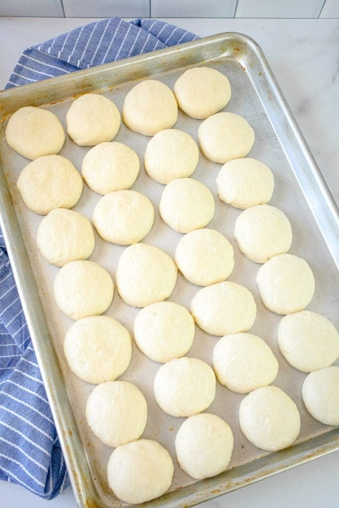 Baking sheet with dinner rolls dough balls on it.
