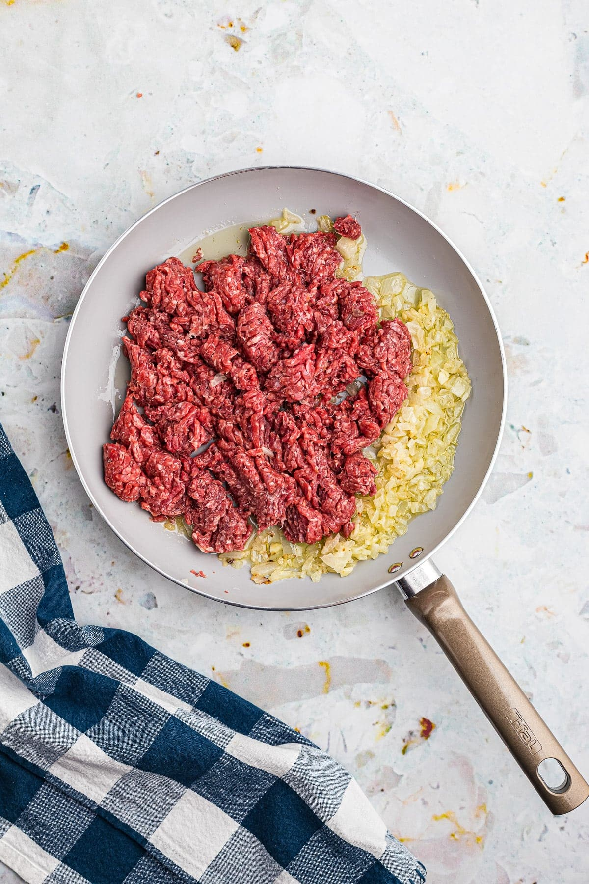 Ground beef, onions and garlic in skillet before browning.