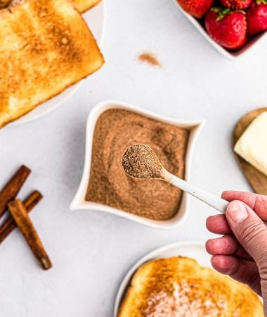 Tiny spoon with cinnamon sugar mixture on it with a bowl of it behind it along with toast and strawberries.