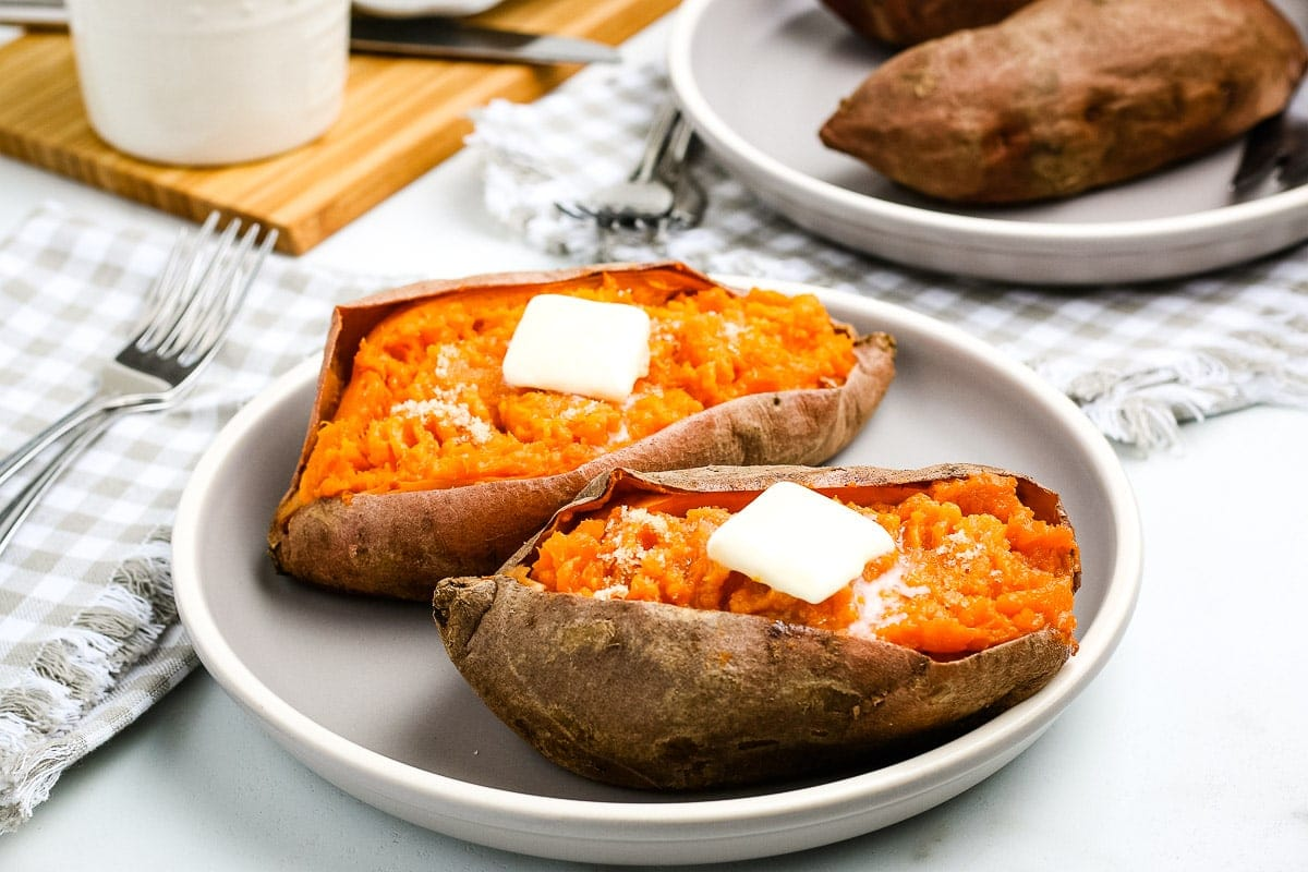 White plate with two sweet potatoes cut open and butter on top