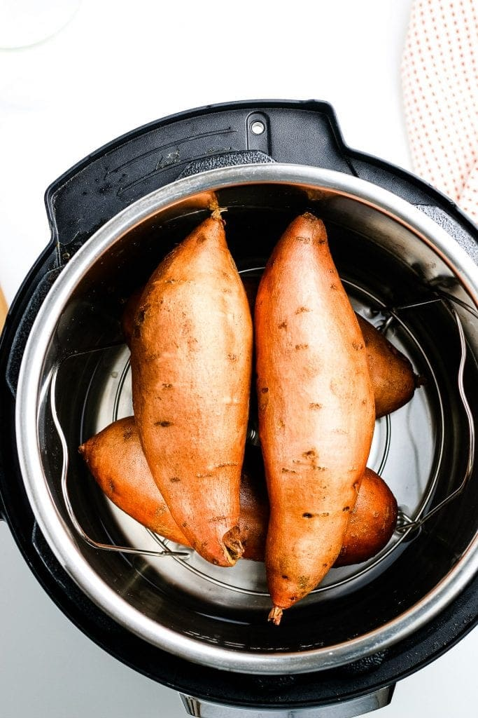 Four sweet potatoes in Instant Pot before cooking
