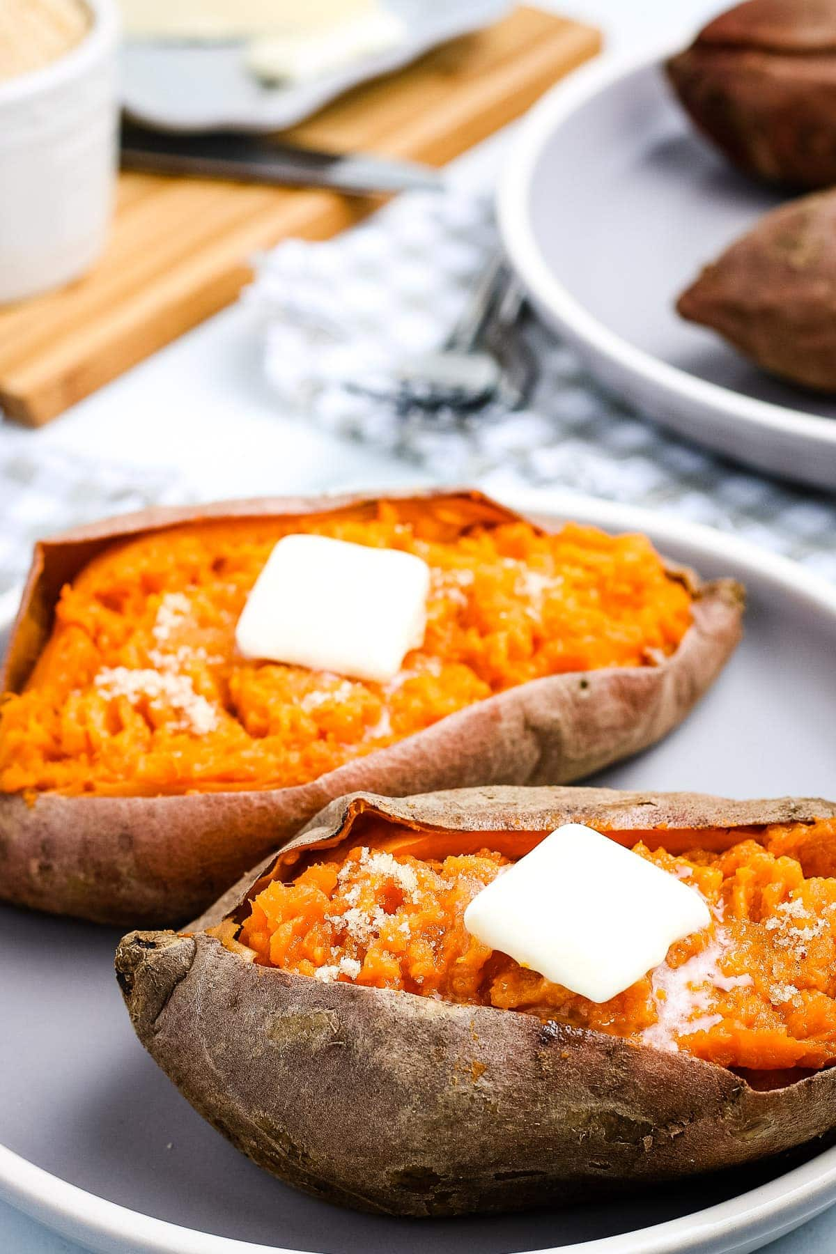 White Plate with two sweet potatoes with a slab of butter on top of each one.