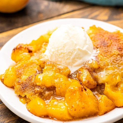 White plate with peach dump cake on it topped with ice cream.