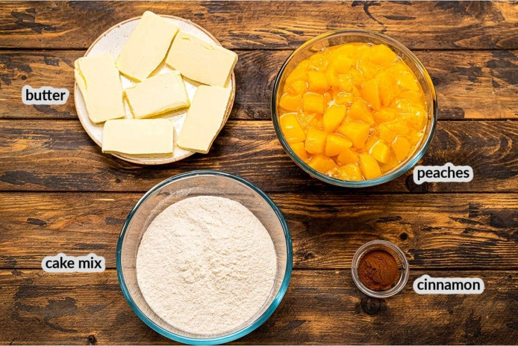 Overhead image showing peach pie filling, butter slabs, cake mix and cinnamon to make dump cake