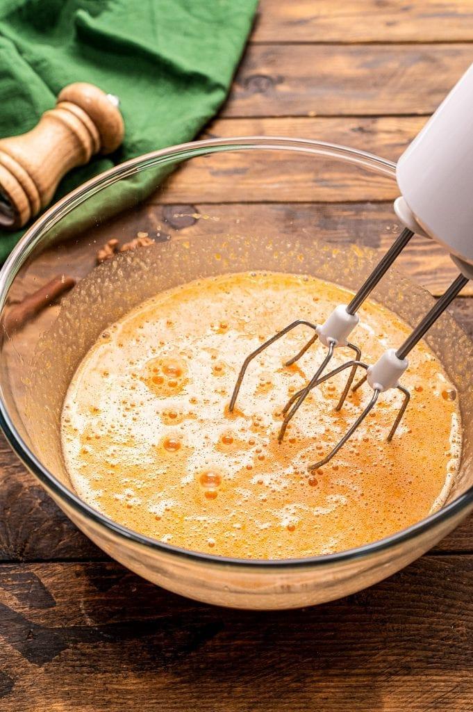 Hand mixer mixing wet ingredients for pumpkin batter