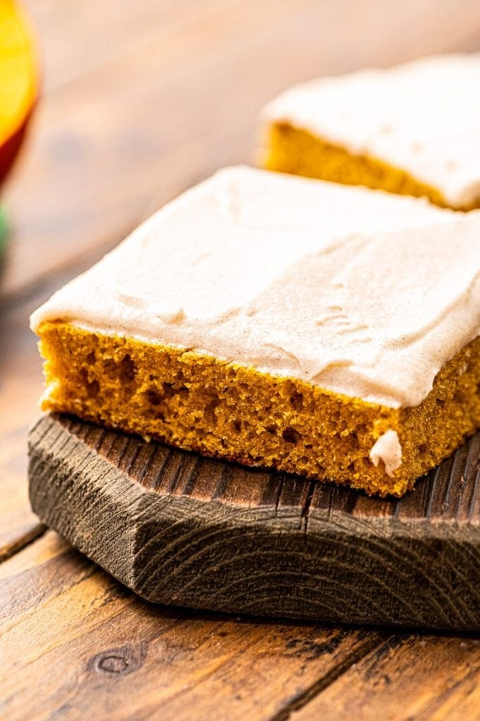 Square Slice of Pumpkin Bars with Cream Cheese Frosting on a wooden cutting board