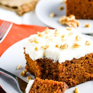 Slice of pumpkin cake on white plate with a fork laying next to it with a bite out of it.