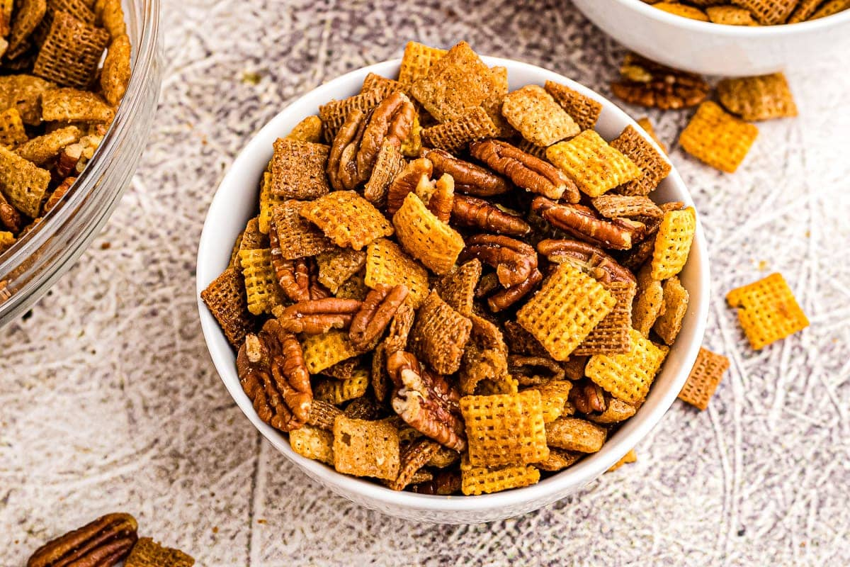 Overhead image of white bowl with pumpkin chex mix in it