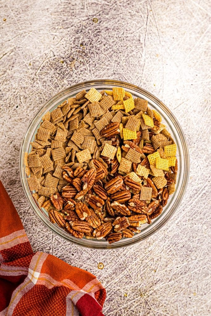 Glass bowl with chex cereals and pecans before stirring.