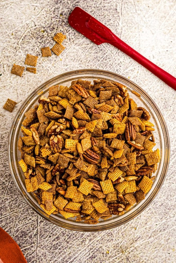 Overhead image of pumpkin chex mix in glass bowl.