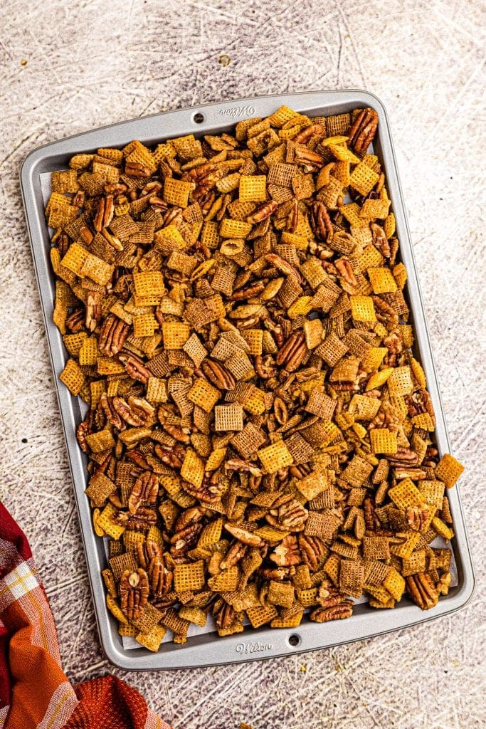 Sheet pan with pumpkin chex mix on it.