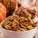 White bowl with pumpkin chex mix in it