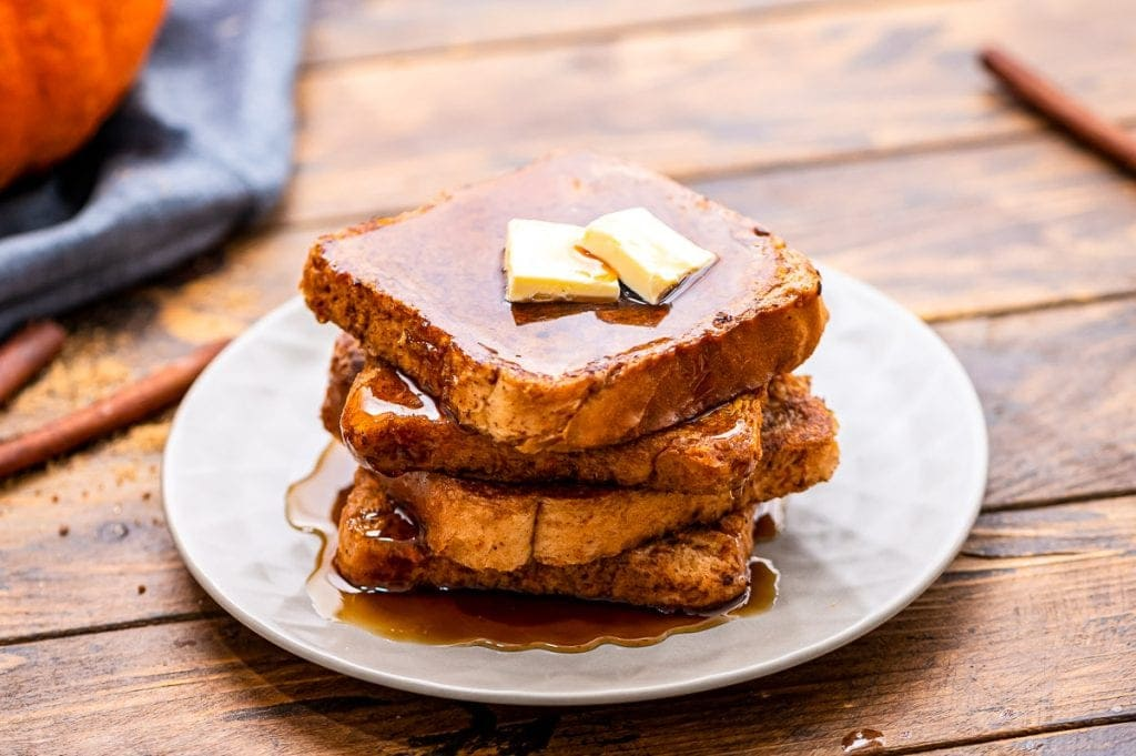 White plate with a stack of french toast on it topped with butter and syrup